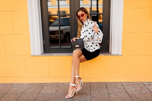 Außenbild der herrlichen frau mit den beinen in der stilvollen frühlingskleidung mit der kleinen tasche, die auf der straße auf gelb aufwirft.