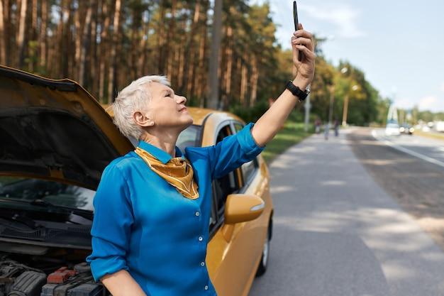Außenbild der unglücklichen frau mittleren alters, die auf straße durch gebrochenes auto mit offener motorhaube steht, die hand mit handy hebt, auf der suche nach netzwerksignal, das versucht, um hilfe zu rufen.