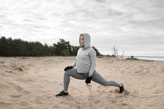 Außenbild des attraktiven schlanken muskulösen jungen weiblichen athleten in der trendigen sportbekleidung, die am sandstrand ausübt, ausfallschritte macht, körper vor dem laufen aufwärmt. sport, fitness, flexibilität und kraft