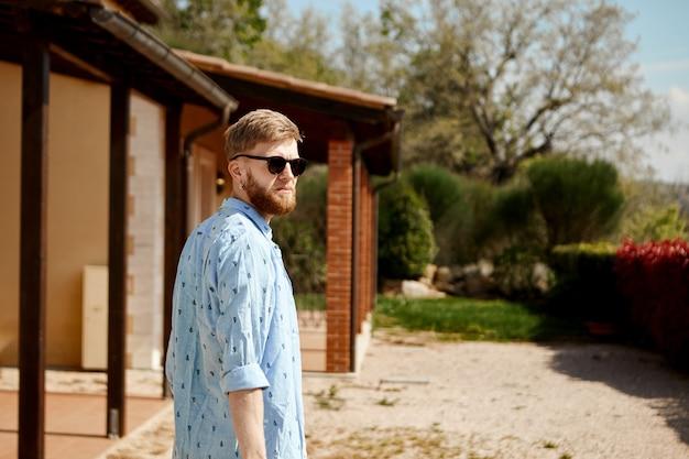 Außenbild des schönen stilvollen jungen europäischen mannes mit dem dicken bart, der sonnigen sommertag verbringt