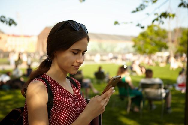 Außenbild des stilvollen teenager-mädchens, das rotes polka-kleid und brillen auf kopf unter verwendung der online-kartenanwendung auf ihrem handy beim rucksackwandern in einem europäischen land trägt. selektiver fokus