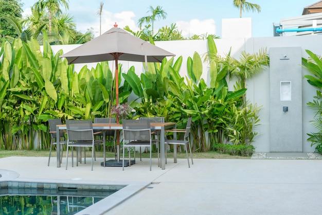 Außendesign außentisch mit sonnenschirm am pool des hauses oder des wohngebäudes