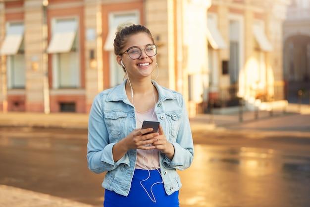 Außenfoto der blonden jungen frau in den gläsern geht durch die stadt, lässig gekleidet in eine jeansjacke und engen blauen rock gekleidet