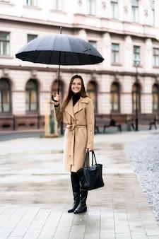 Außenfoto der brünetten dame, die mit schwarzem regenschirm im regnerischen herbsttag aufwirft. mode street style porträt. trägt eine dunkle freizeithose, einen weißen pullover und einen cremigen mantel. modekonzept.