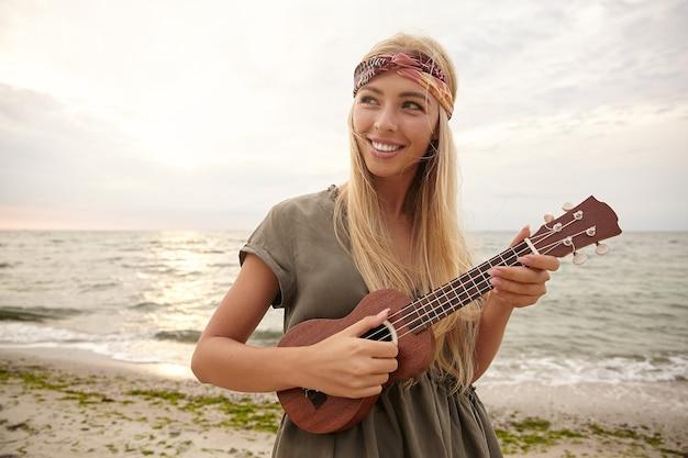 Außenfoto der jungen charmanten weißköpfigen frau im stirnband, die glücklich lächelt, während sie auf kleiner gitarre spielt und am hellen warmen tag über meer geht