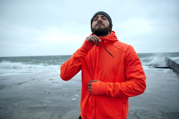 Außenfoto des jungen brünetten mannes mit dem üppigen bart, der über meerblick an stürmischem grauem tag steht und seinen warmen orange sportlichen mantel zippt. fitness- und sportkonzept.