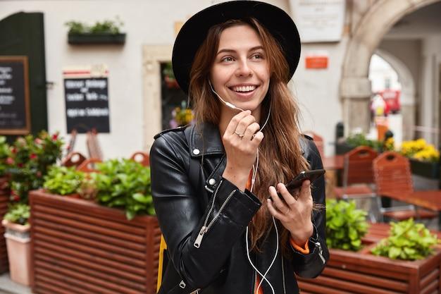 Außenfoto des lächelnden weiblichen reisenden hat gespräch über kopfhörer, hält handy, zufrieden mit gutem ton
