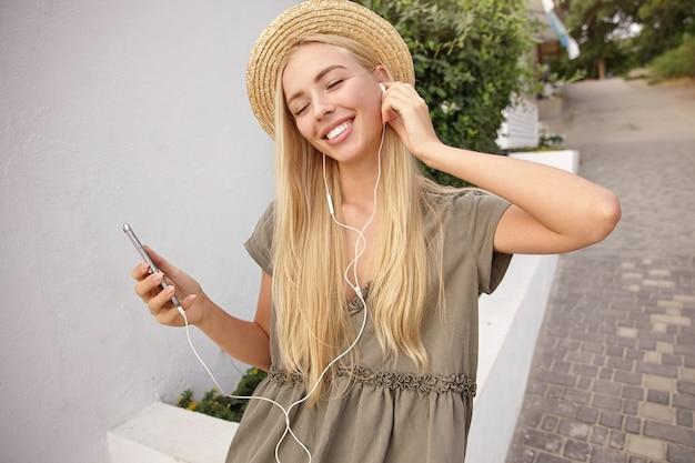 Außennahaufnahme der attraktiven glücklichen frau, die musik mit kopfhörern hört, während durch grüne straße geht, musikspur genießt