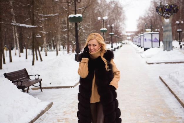 Außennahaufnahmefoto des jungen schönen glücklichen lächelnden mädchens, das auf straße im winter geht