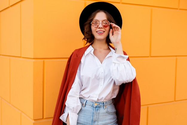 Außennahaufnahmeporträt der glückseligen brünetten kurzhaarigen frau, die über gelber wand aufwirft. trendiger hut, rosa brille, weiße bluse und jeans.