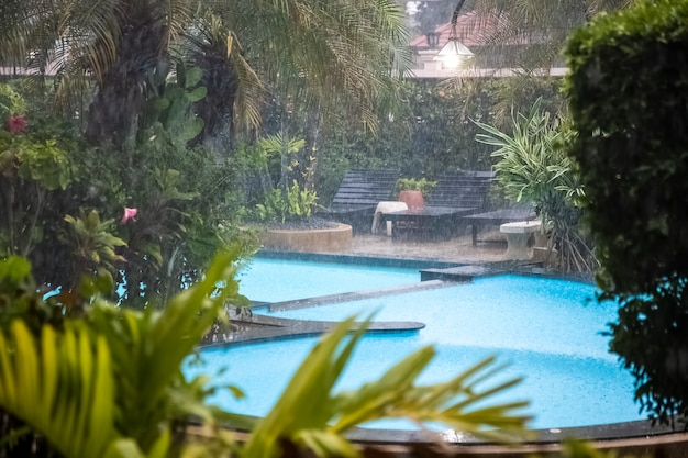 Außenpool im tropischen garten des hotels bei starkem regen