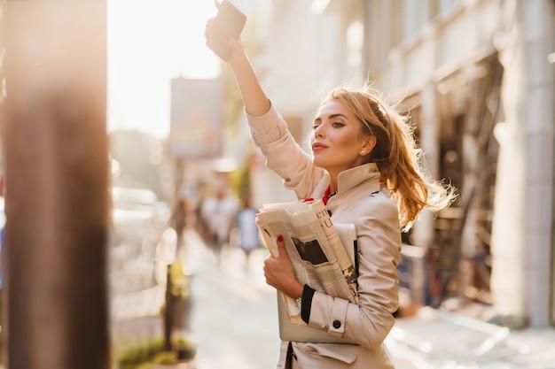 Außenporträt der aktiven geschäftsfrau in der trendigen kleidung, die auf taxi am morgen wartet