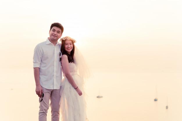 Außenporträt der asiatischen braut und des bräutigams, die aufwerfen