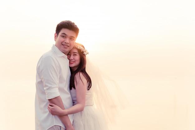 Außenporträt der asiatischen braut und des bräutigams suchen