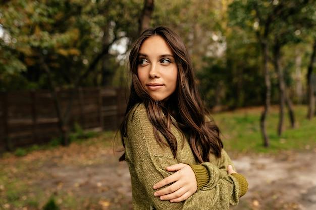 Außenporträt der bezaubernden hübschen europäischen frau mit dem langen gewellten haar, das grünen pullover trägt, der im park geht