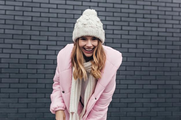 Außenporträt der blithesome frau im rosa mantel. attraktives blondes mädchen im winterhut, der vor ziegelmauer aufwirft.