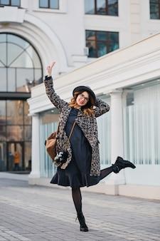 Außenporträt der eleganten jungen dame mit braunem rucksack, der mantel und hut trägt. attraktive frau mit lockigem haar, die springend spricht und spaß hat.
