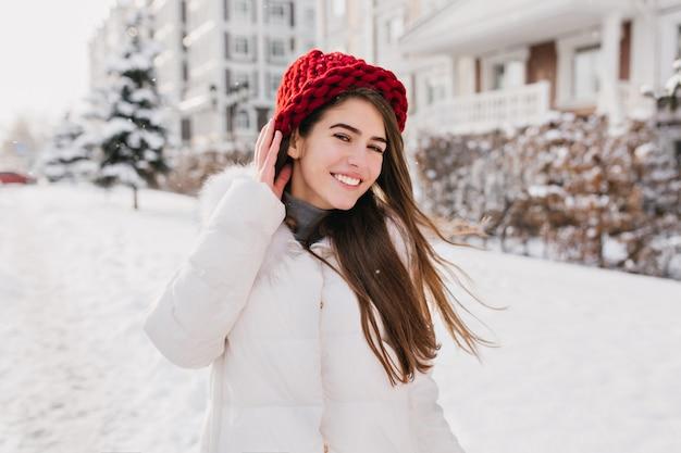 Außenporträt der erfreuten langhaarigen dame in der roten strickmütze, die im verschneiten wochenende die straße entlang geht. foto der lachenden niedlichen dame im weißen wintermantel, der spaß am kalten morgen hat ..