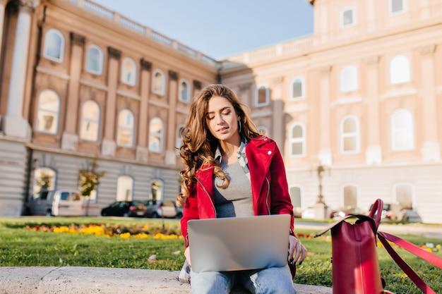 Außenporträt der ernsthaften gelockten studentin, die mit laptop auf dem boden sitzt
