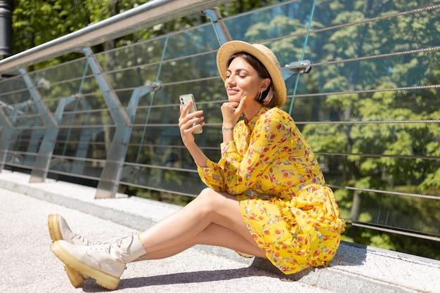 Außenporträt der frau im gelben sommerkleid, das auf brücke mit handy schaut, das auf bildschirm mit einem lächeln schaut