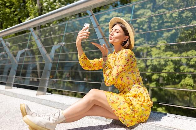 Außenporträt der frau im gelben sommerkleid, das auf brücke sitzt, nehmen selfie auf handy