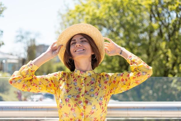 Außenporträt der frau im gelben sommerkleid und im hut auf der brücke, die kopfhaar schütteln fliegende erhobene händeaugen geschlossen
