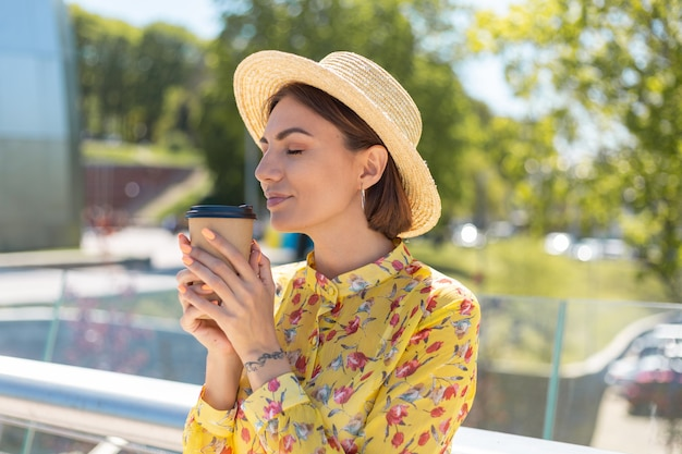 Außenporträt der frau im gelben sommerkleid und im hut mit der tasse kaffee, die sonne genießt