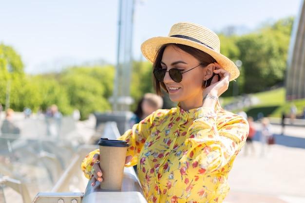 Außenporträt der frau im gelben sommerkleid und im hut mit tasse kaffee, die sonne genießt, steht auf brücke mit stadt erstaunliche ansicht