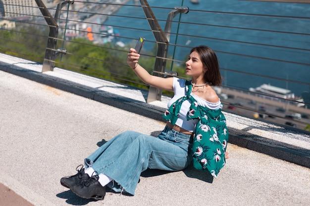 Außenporträt der frau im lässigen grünen hemd am sonnigen tag steht auf brücke, die auf telefonbildschirm schaut, nimmt selfie, machen videoanruf