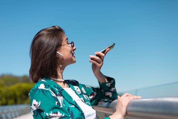 Außenporträt der frau im lässigen grünen hemd am sonnigen tag steht auf brücke, die sprachnachricht drahtlose bluetooth-kopfhörer in den ohren aufzeichnet