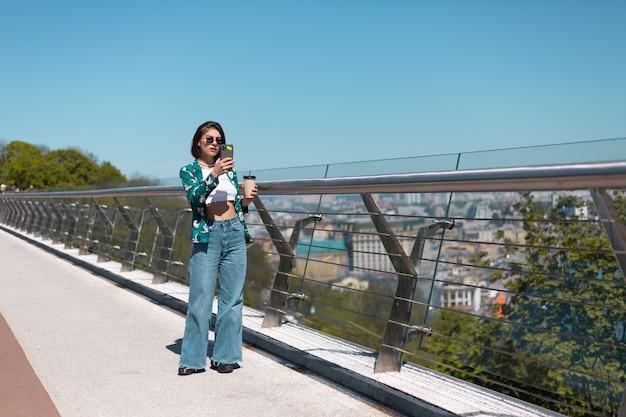 Außenporträt der frau im lässigen grünen hemd und in den jeans am sonnigen tag geht auf brücke mit tasse kaffee, der auf telefonbildschirm schaut