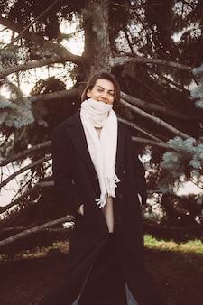 Außenporträt der frau im park, der schwarzen wintermantel und weißen schal trägt