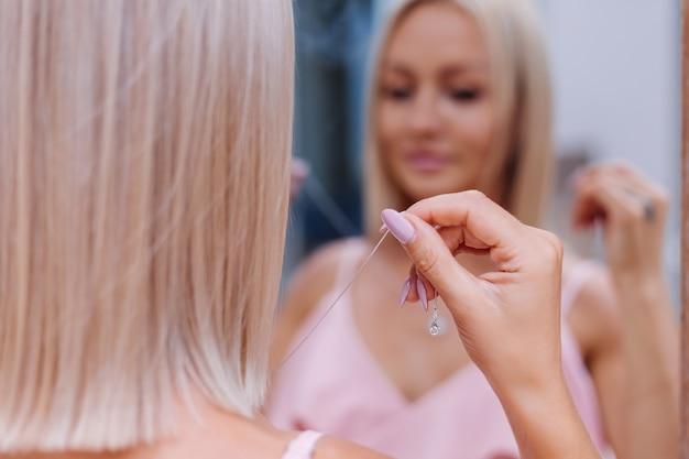 Außenporträt der frau im rosa romantischen kleid, das halskette trägt