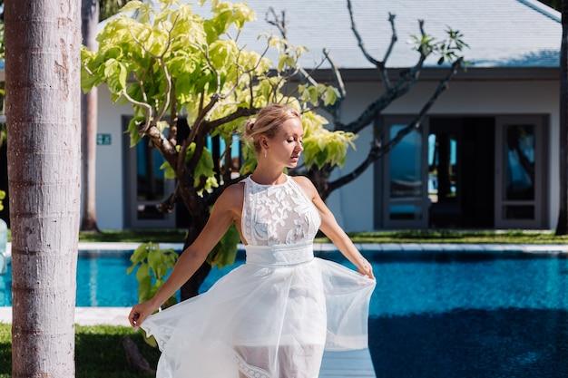 Außenporträt der frau im weißen hochzeitskleid an der villa im sonnigen tag, tropische ansicht