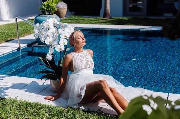 Außenporträt der frau im weißen hochzeitskleid, das nahe dem blauen schwimmbad mit blumen sitzt