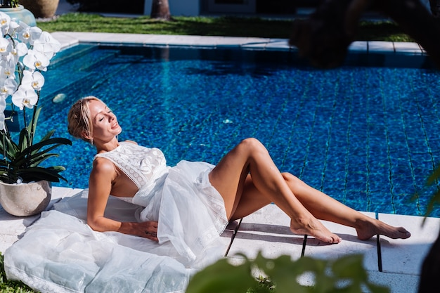 Außenporträt der frau im weißen hochzeitskleid, das nahe dem blauen schwimmbad mit blumenorchidee sitzt