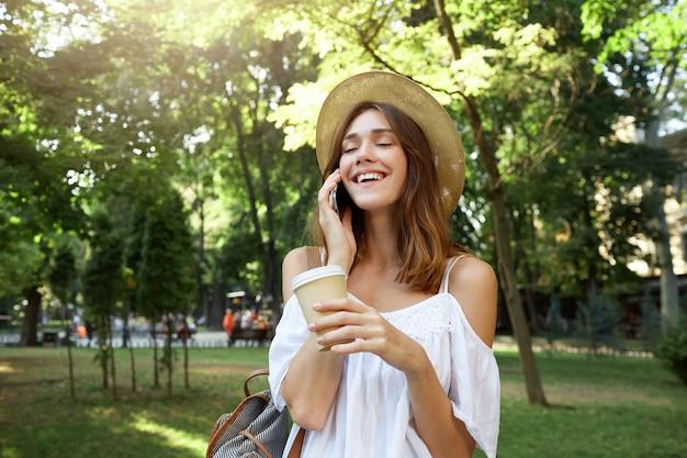 Außenporträt der fröhlichen attraktiven jungen frau mit geschlossenen augen, die tasse kaffee zum mitnehmen halten, trägt stilvollen hut, der auf handy spricht und im park im sommer lacht