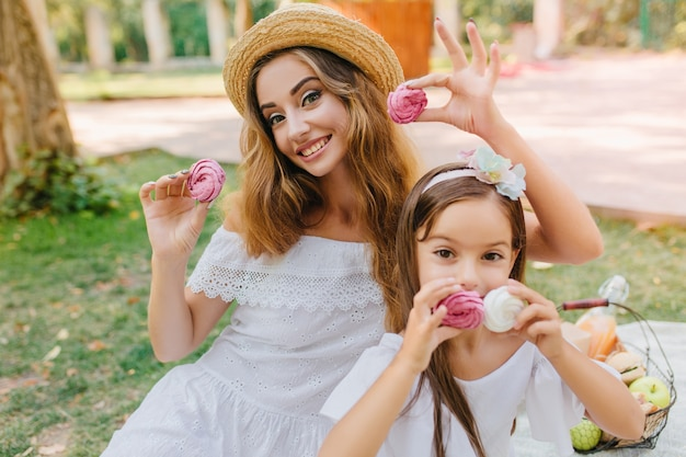Außenporträt der fröhlichen jungen frau im weinlesekleid und im freudigen mädchen mit dem band im dunklen haar, das auf natur aufwirft. glückliche mutter und tochter, die leckere kekse im park halten.