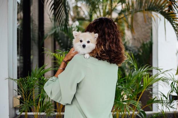 Außenporträt der gelockten europäischen gebräunten frau hält glücklichen pomeranischen spitzhund