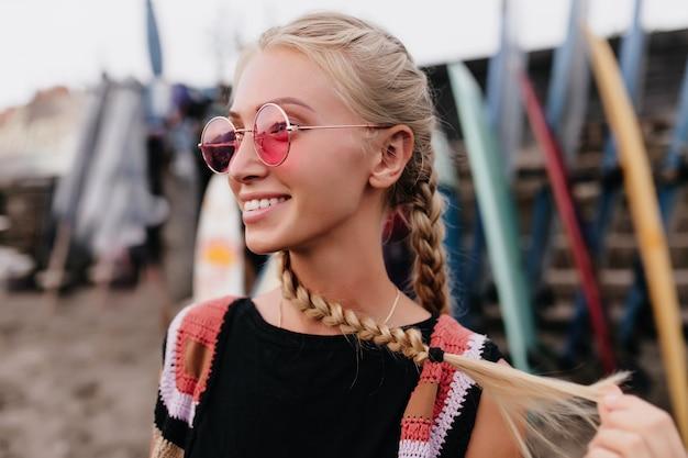 Außenporträt der glücklichen blonden frau in der rosa sonnenbrille, die weg auf unschärfehintergrund schaut.
