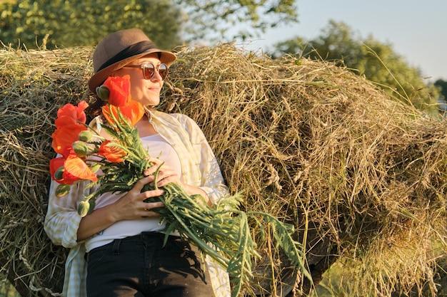Außenporträt der glücklichen reifen frau mit einem blumenstrauß von mohnblumen