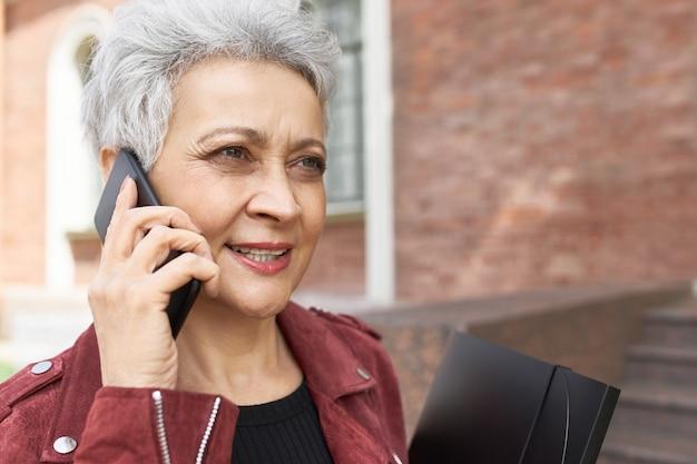 Außenporträt der gut aussehenden selbstbewussten geschäftsfrau mittleren alters, die auf handy spricht