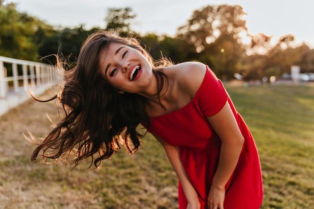 Außenporträt der gut gelaunten jungen dame im roten kleid, das glück ausdrückt. foto des erfreuten mädchens mit braunem haar, das auf natur aufwirbelt