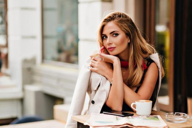 Außenporträt der gutaussehenden jungen frau mit gebräunter haut, die mit sanftem lächeln beim ruhen im café aufwirft