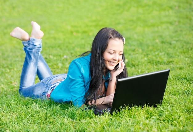 Außenporträt der jungen frau, die unter verwendung eines laptops liegt