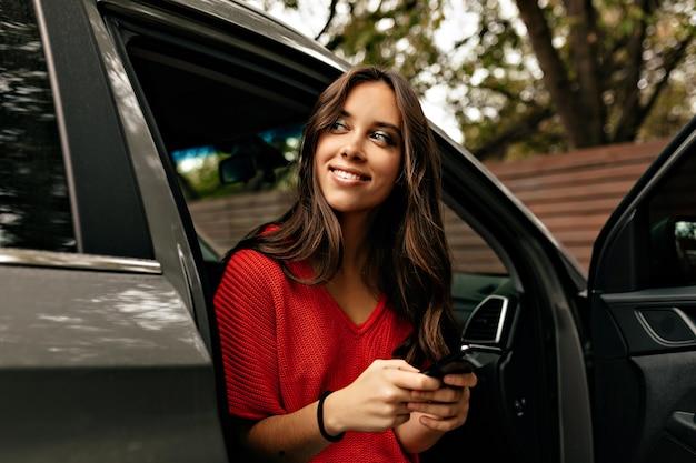 Außenporträt der jungen stilvollen frau mit dem langen gewellten haar unter verwendung des smartphones im auto
