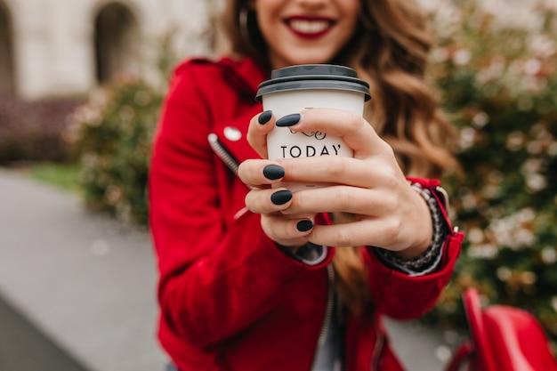 Außenporträt der lachenden jungen frau mit schwarzer maniküre, die tasse kaffee hält