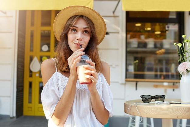 Außenporträt der lächelnden attraktiven jungen frau trägt stilvollen sommerhut und weißes kleid, fühlt sich glücklich, geht in der stadt spazieren und trinkt kaffee zum mitnehmen