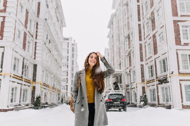 Außenporträt der langhaarigen frau im trendigen grauen mantel beim einkaufen im verschneiten tag. wunderschöne blonde frau im stilvollen outfit, die zeit in der stadt im winterwochenende verbringt.