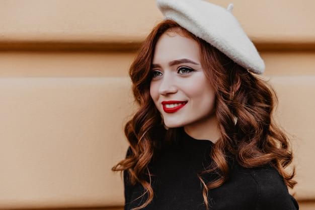 Außenporträt der modischen kaukasischen dame mit gewelltem ingwerhaar. hübsches französisches mädchen im barett, das auf der straße lacht.